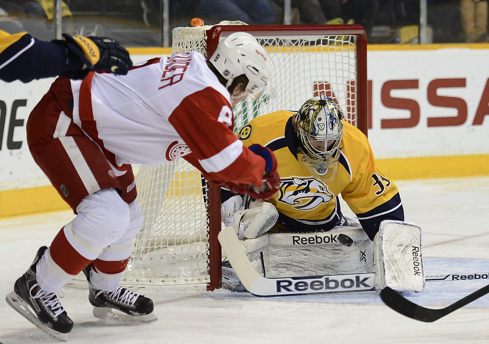 Detroit Red Wings left wing Justin Abdelkader, left, flips the puck past Nashville Predators goalie Marek Mazanec (39), of the Czech Republic, for a goal in the first period of an NHL hockey game on Monday, Dec. 30, 2013, in Nashville, Tenn. (AP Photo/Mark Zaleski)