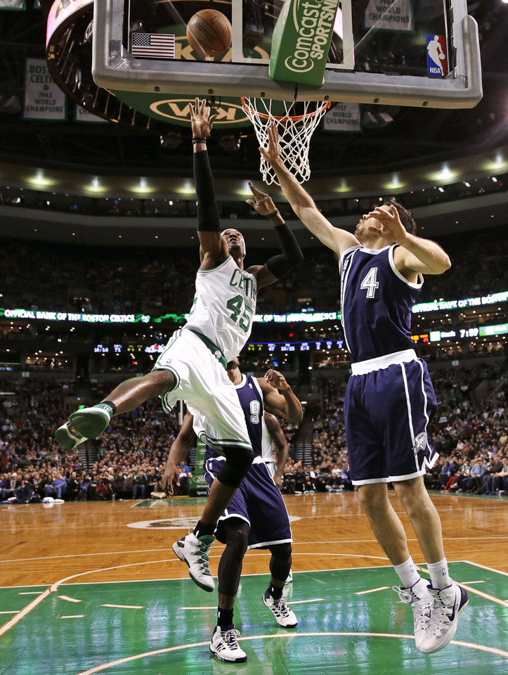 Photo - Boston Celtics forward Gerald Wallace (45) shoots against Oklahoma City Thunder forward Nick Collison (4) during the first half of an NBA basketball game in Boston, Friday, Jan. 24, 2014. (AP Photo/Charles Krupa)