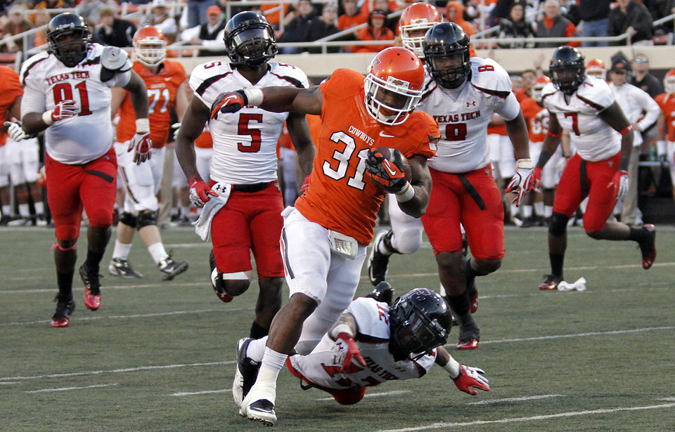 Photo - Oklahoma State's Jeremy Smith (31) runs past Texas Tech's D.J. Johnson (12) for a touchdown during the college football game between the Oklahoma State University Cowboys (OSU) and Texas Tech University Red Raiders (TTU) at Boone Pickens Stadium on Saturday, Nov. 17, 2012, in Stillwater, Okla.   Photo by Chris Landsberger, The Oklahoman
