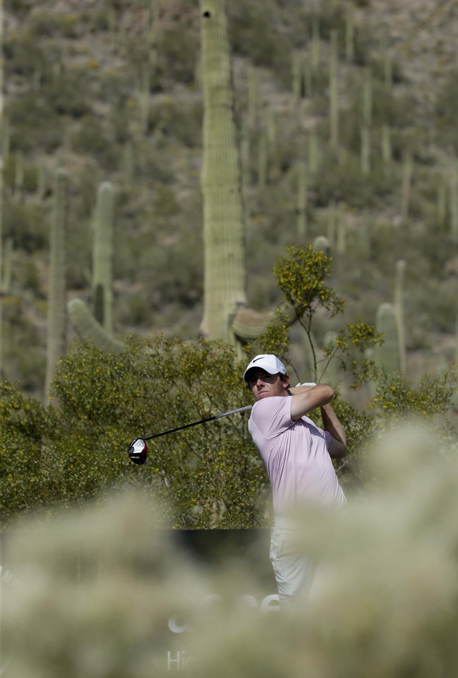 Photo - Rory McIlroy, of Northern Ireland, watches his tee shot during a practice round for the Match Play Championship golf tournament Tuesday, Feb. 18, 2014, in Marana, Ariz. (AP Photo/Chris Carlson)