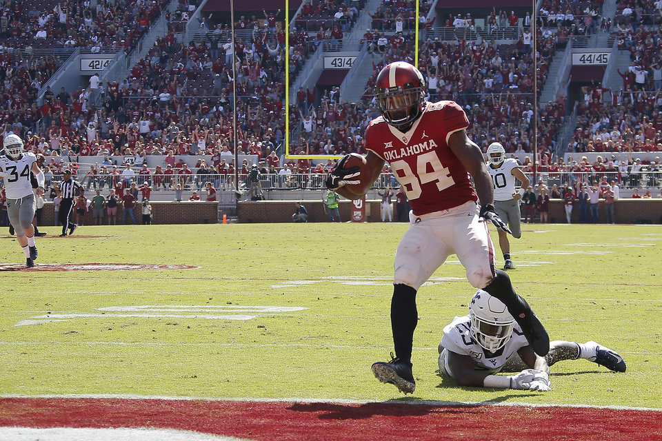 Photo - Oklahoma's Lee Morris (84) scores a touchdown in frot of West Virginia's Tykee Smith (23) during a college football game between the University of Oklahoma Sooners (OU) and the West Virginia Mountaineers at Gaylord Family-Oklahoma Memorial Stadium in Norman, Okla, Saturday, Oct. 19, 2019. Oklahoma won 52-14. [Bryan Terry/The Oklahoman]