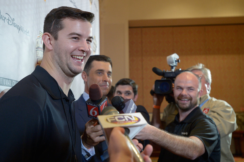 Photo - Alabama quarterback AJ McCarron, left, answers questions during a media availability prior to the College Football Awards show in Lake Buena Vista, Fla., Wednesday, Dec. 11, 2013. (AP Photo/Phelan M. Ebenhack)