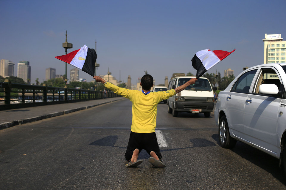 Photo - A man waves Egyptian flags as he kneels on a bridge that leads to Tahrir Square in Cairo, Egypt, Friday, July 26, 2013. Political allies of Egypt's military lined up behind its call for huge rallies Friday to show support for the country's top general, pushing toward a collision with Islamist opponents demanding the return of Mohammed Morsi, the nation's ousted president. (AP Photo/Hassan Ammar)