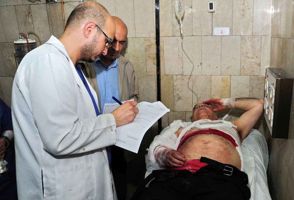 Photo - In this photo released by the Syrian official news agency SANA, a Syrian doctor, left, treats an injured man, right, who was wounded at the open-air cafeteria at Damascus University in the central Baramkeh district, in Damascus, Syria, Thursday, March 28, 2013. Mortar shells slammed into a cafeteria at Damascus University, killing several people and wounding scores, according to state media and an official. It was the deadliest in a string of such attacks on President Bashar Assad's seat of power, state media and an official said. (AP Photo/SANA)