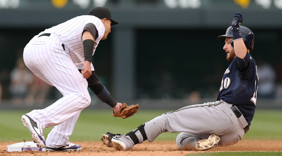 Photo - Colorado Rockies shortstop Troy Tulowitzki, left, tags out Milwaukee Brewers' Jonathan Lucroy who waas trying to advance to second base on his single that scored two runs in the fifth inning of a baseball game in Denver, Sunday, June 22, 2014. (AP Photo/David Zalubowski)