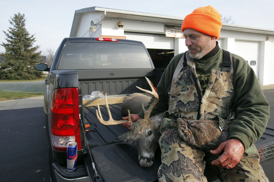 Earl Agy, of Allegan, poses with the 8-point buck he shot in Van Buren County of the first day of firearm deer season Thursday, Nov. 15, 2012 at the DNR check in Plainwell, Mich. (AP Photo/The Kalamazoo Gazette, Mark Bugnaski) ALL LOCAL TV OUT; LOCAL TV INTERNET OUT
