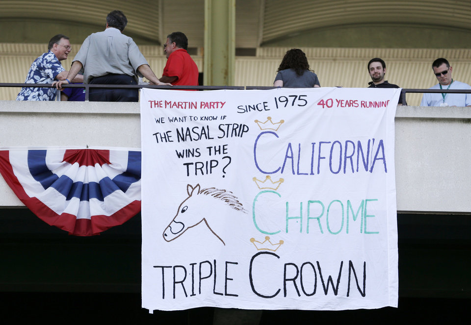 Photo - Fans gather near a sign supporting race horse California Chrome at Belmont Park, Saturday, June 7, 2014, in Elmont, N.Y. California Chrome is the favorite to win the Belmont Stakes horse race and Triple Crown later in the day. (AP Photo/Seth Wenig)