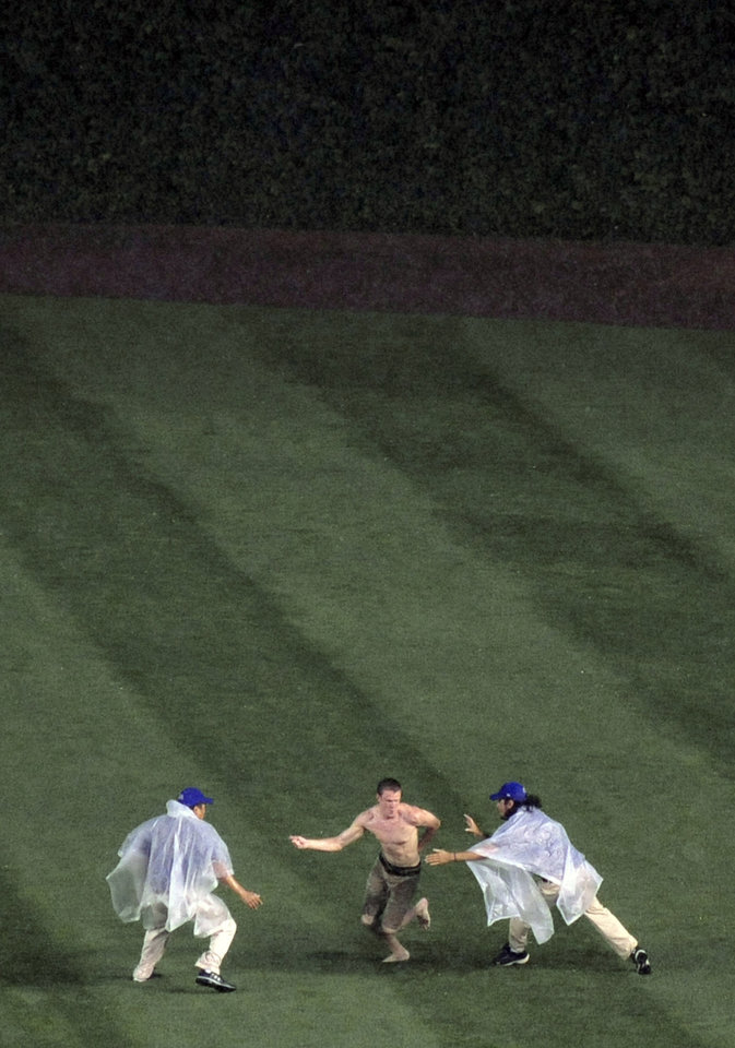 Photo - A fan, center, runs out on the field during a rain delay before a baseball game between the Chicago Cubs and the Pittsburgh Pirates in Chicago, Saturday, June 21, 2014. (AP Photo/Paul Beaty)