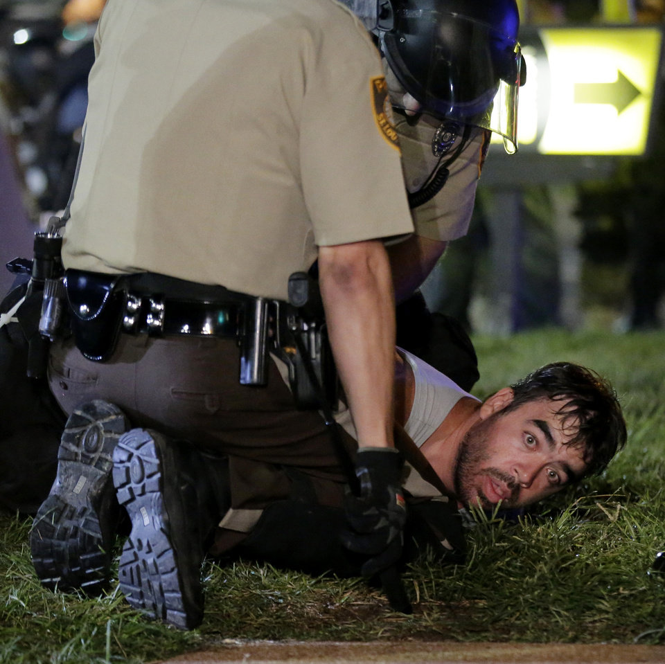 Photo - A man is detained by police during a protest Monday, Aug. 18, 2014, for Michael Brown, who was killed by a police officer Aug. 9 in Ferguson, Mo. Brown's shooting has sparked more than a week of protests, riots and looting in the St. Louis suburb. (AP Photo/Charlie Riedel)