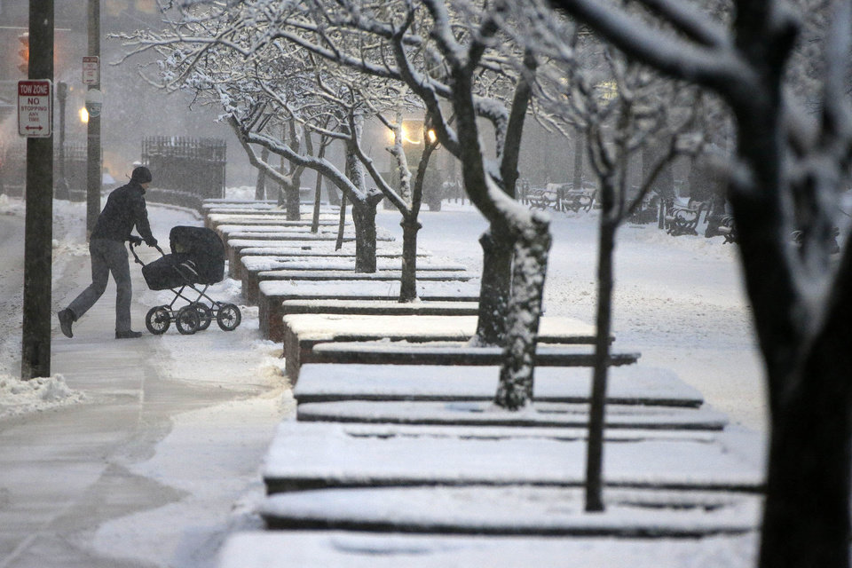 Photo - A man wheels a stroller through snow in the Boston Commons early Friday evening, Feb. 8, 2013 in Boston. Snow began falling across the Northeast on Friday, ushering in what was predicted to be a huge, possibly historic blizzard and sending residents scurrying to stock up on food and gas up their cars. The storm could dump 1 to 3 feet of snow from New York City to Boston and beyond.  (AP Photo/Gene J. Puskar)
