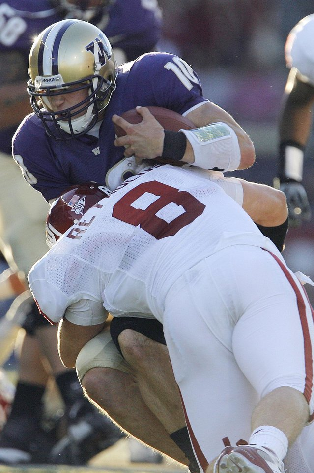 Photo - Oklahoma's Ryan Reynolds (8) stops Washington quarterback Jake Locker (10) in the first half during the college football game between Oklahoma and Washington at Husky Stadium in Seattle, Wash., Saturday, September 13, 2008. BY NATE BILLINGS, THE OKLAHOMAN