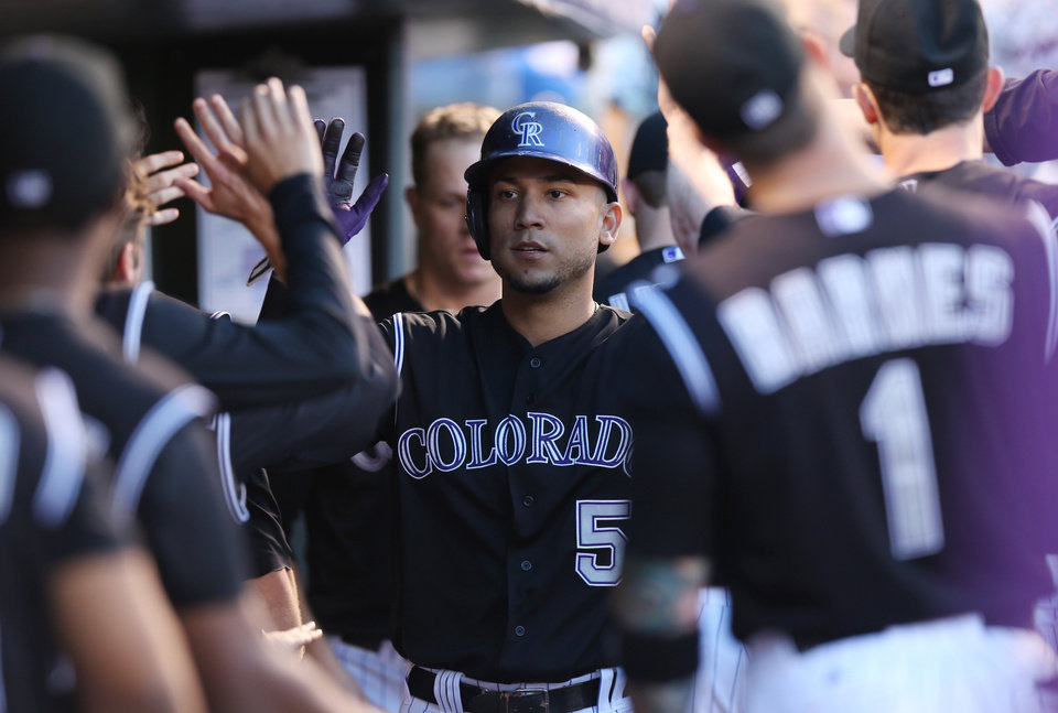 Photo - Colorado Rockies' Carlos Gonzalez, center, is congratulated by teammates after scoring on a triple by Corey Dickerson against the Chicago Cubs in the fourth inning of the Rockies' 13-4 victory in a baseball game in Denver on Wednesday, Aug. 6, 2014. (AP Photo/David Zalubowski)
