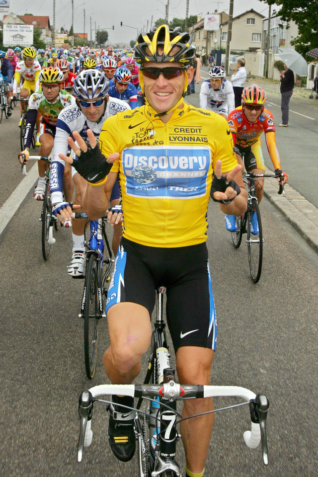 Photo - FILE - In this July 24, 2005, file photo, overall leader Lance Armstrong signals seven for his seventh straight win in the Tour de France cycling race as he pedals during the 21st and final stage of the race between Corbeil-Essonnes, south of Paris, and the French capital. Armstrong confessed to using performance-enhancing drugs to win the Tour de France during a taped interview with Oprah Winfrey that aired Thursday, Jan. 17, 2013, reversing more than a decade of denial. Armstrong called his run to seven Tour de France titles