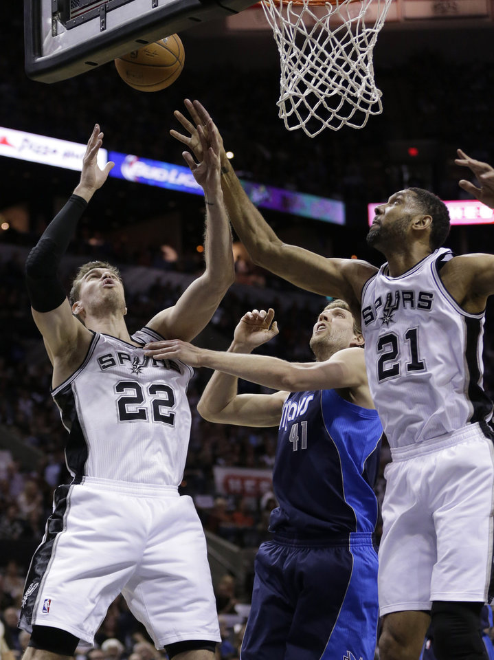 Photo - San Antonio Spurs' Tiago Splitter (22), of Brazil, and Tim Duncan (21) reach over Dallas Mavericks' Dirk Nowitzki, center, of Germany, for a rebound during the first half of Game 5 of the opening-round NBA basketball playoff series on Wednesday, April 30, 2014, in San Antonio. San Antonio won 109-103. (AP Photo/Eric Gay)