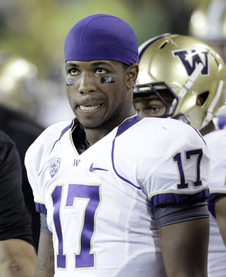 Washington quarterback Keith Price looks at the scoreboard after an Oregon touchdown during the second half of their NCAA college football game in Eugene, Ore., Saturday, Oct. 6, 2012. Oregon beat Washington 52-21.(AP Photo/Don Ryan)
