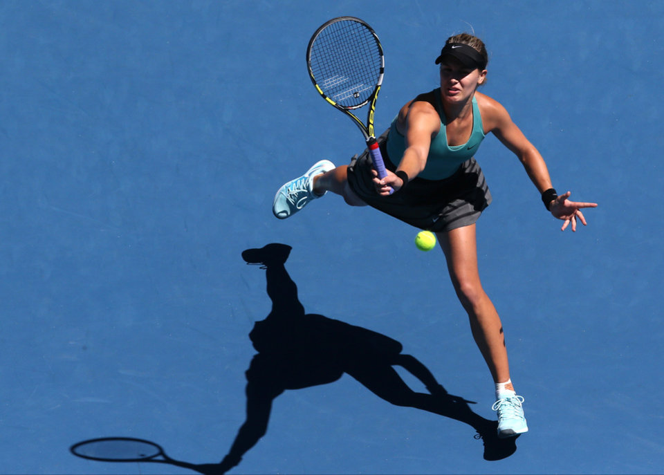 Photo - Eugenie Bouchard of Canada makes a forehand return during her quarterfinal against Ana Ivanovic of Serbia at the Australian Open tennis championship in Melbourne, Australia, Tuesday, Jan. 21, 2014.(AP Photo/Eugene Hoshiko)