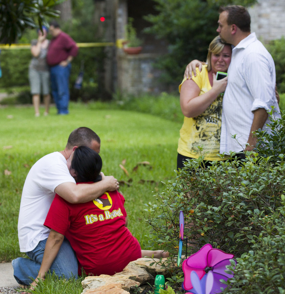 Photo - Neighbors embrace each other following a shooting Wednesday, July 9, 2014, in Spring, Texas. Deputies have cornered a man suspected in a shooting at a suburban Houston home that resulted in multiple fatalities. (AP Photo/Houston Chronicle, Brett Coomer)