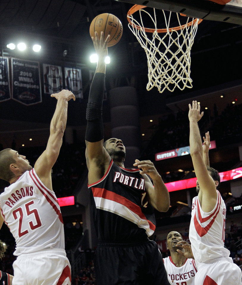 Portland Trail Blazers forward LaMarcus Aldridge (12) drives to the basket past  Houston Rockets forward Chandler Parsons (25) during the first half of an NBA basketball game, Monday, Jan. 20, 2014, in Houston. (AP Photo/Bob Levey)