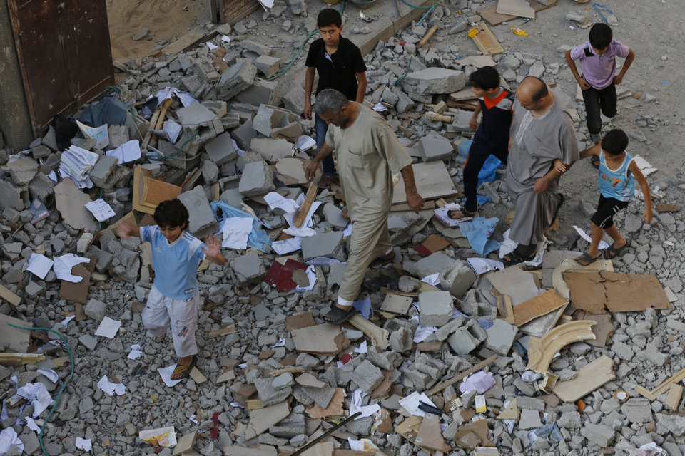 Photo - Residents walk on debris from a destroyed house in Beit Lahiya, in northern Gaza strip, Saturday, July 19, 2014. A Gaza health official says the death toll from Israel's 12-day offensive against Hamas militants has topped 300. (AP Photo/Lefteris Pitarakis)