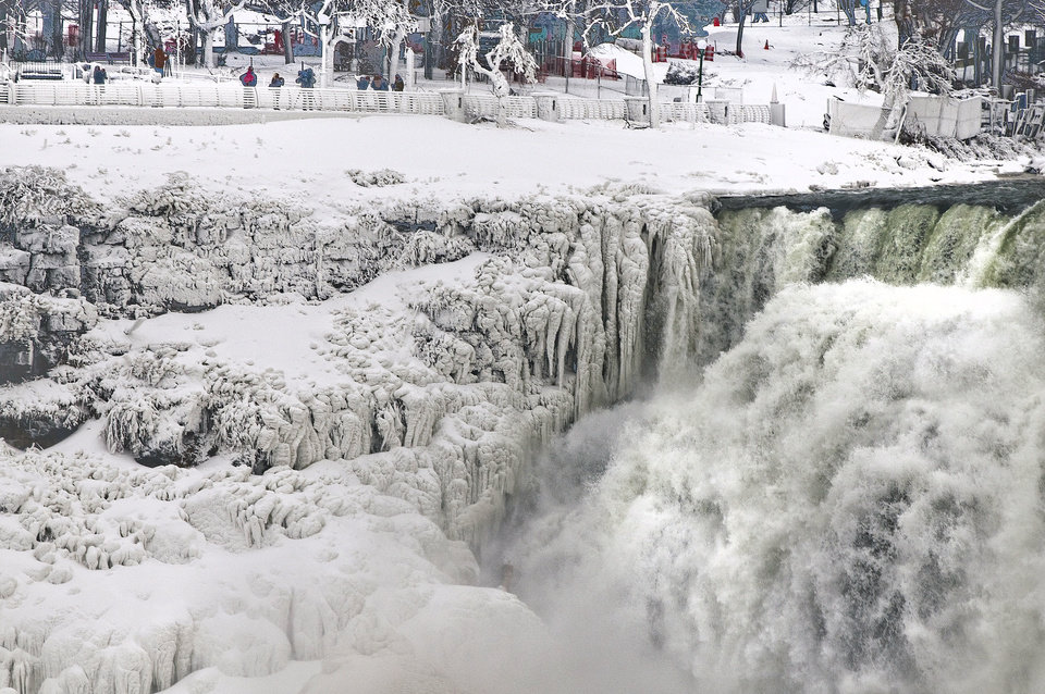 Photo - Ice forms along the areas of Niagara Falls and Niagara Falls State Park in Niagara Falls, N.Y., photographed from Niagara Falls Ontario, Canada.  Niagara Falls hasn't frozen over, but it has become an icy spectacle, thanks to a blast of arctic wind and cold that blew around and froze the mist on surfaces and landscaping. Despite the urban legends, Niagara Falls doesn't freeze solid in the winter, tourism officials say.  A section of the American Falls, one of three waterfalls that make up the natural attraction, has frozen. The Niagara River rapids and larger Horseshoe Falls continue to flow unimpeded.  (AP Photo/The Niagara Gazette, James Neiss)  BUFFALO NEWS OUT; BATAVIA DAILY NEWS OUT