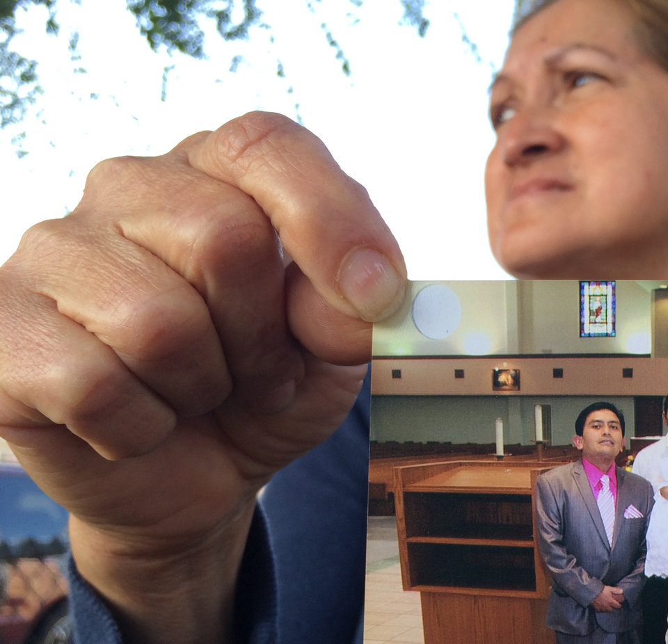 Photo - Neighbor Maria Sanchez holds a Jan. 29, 2012 photo of her neighbor Isidro Garcia at his daughter's third birthday at Bell Gardens church, while talking to the media on Wednesday, May, 21, 2014 in Bell Gardens, Calif. Garcia allegedly kidnapped a 15-year-old girl in Santa Ana in 2004 then repeatedly physically and sexually assaulted her over the course of 10 years. (AP Photo/Damian Dovarganes)