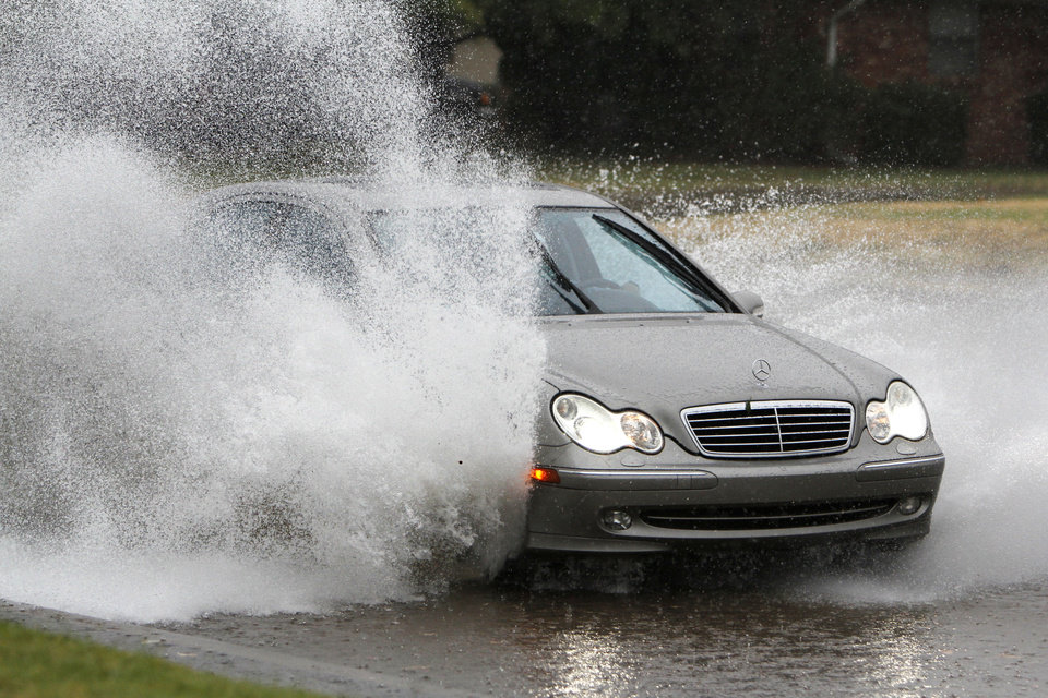A car plows through flash flood waters  on Britton Road near the Hefner Parkway in Oklahoma City, OK, Saturday, August 18, 2012,  By Paul Hellstern, The Oklahoman
