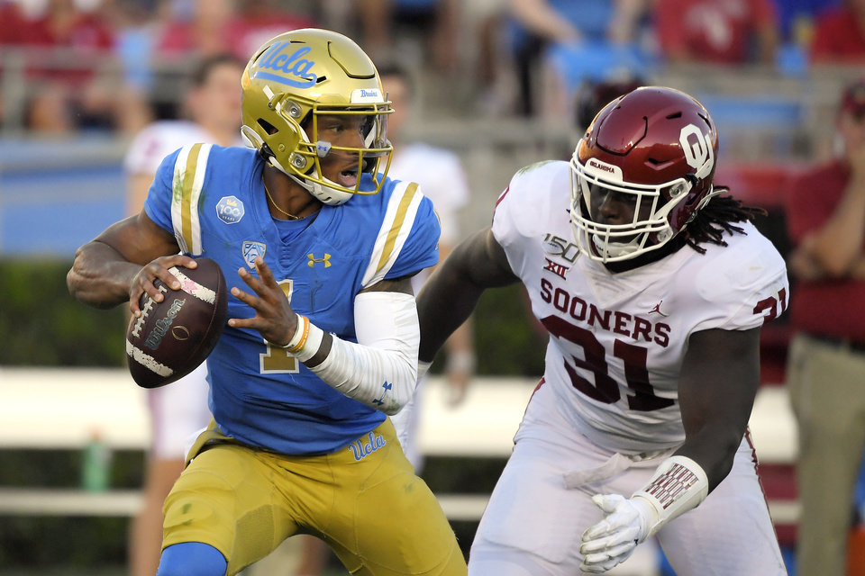 Photo - UCLA quarterback Dorian Thompson-Robinson, gets set to pass before being sacked by Oklahoma linebacker Jalen Redmond during the first half of an NCAA college football game Saturday, Sept. 14, 2019, in Pasadena, Calif. (AP Photo/Mark J. Terrill)