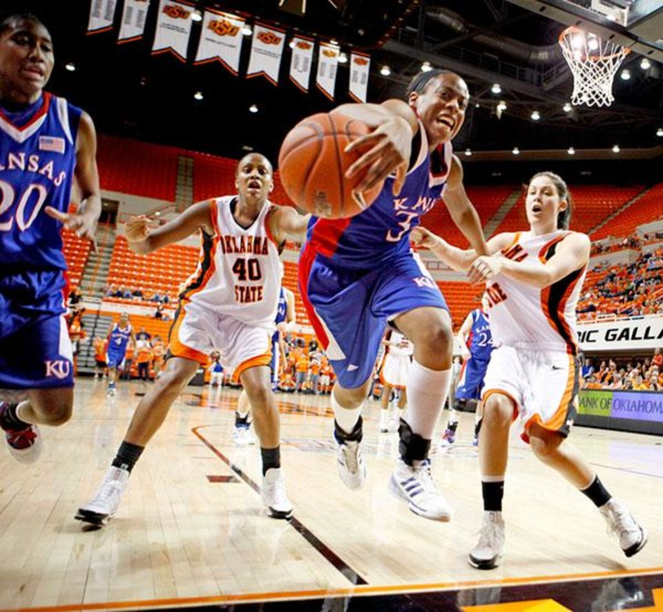 Porscha Weddington of Kasas chases the ball between OSU's Shyvon Spears, left, and Tegan Cunningham during the women's NCAA college basketball game between Oklahoma State and Kansas in Stillwater, Okla., Wednesday, Feb. 25, 2009. PHOTO BY BRYAN TERRY, THE OKLAHOMAN