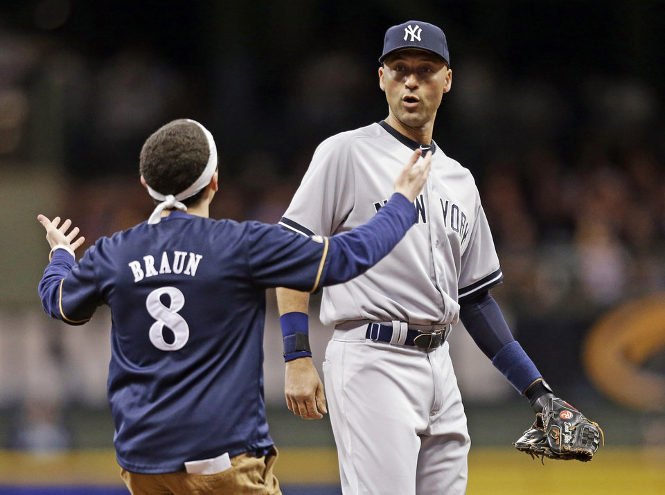 Photo - A fan runs out on the field to New York Yankees' Derek Jeter in the sixth inning of a baseball game against the Milwaukee Brewers, Friday, May 9, 2014, in Milwaukee. (AP Photo/Jeffrey Phelps)