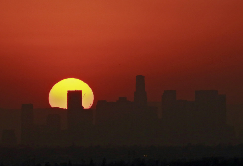 Photo - In a view from Whittier, Calif., the sun sets behind a hazy downtown Los Angeles after a week of high temperatures from the view Tuesday, Aug. 18, 2015. (AP Photo/Nick Ut)