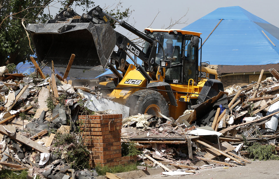 Photo - Victor Muto with Team Rubicon uses a front loader to finish demolition on a home on SW 148 in Moore.  BRYAN TERRY - THE OKLAHOMAN