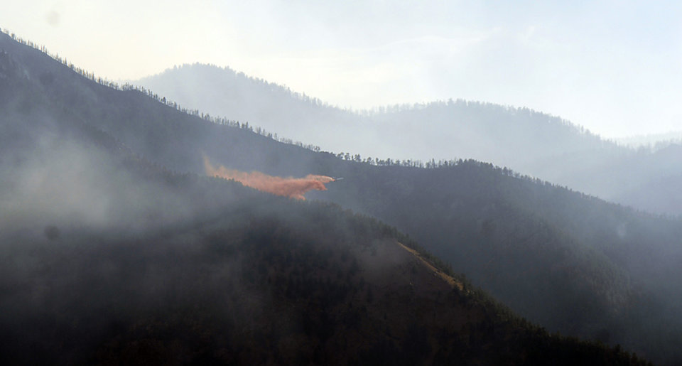 Photo -   A slurry bomber drops fire retardant on the Waldo Canyon Fire Wednesday, June 27, 2012, in Colorado Springs, Colo. The wildfire doubled in size overnight to about 24 square miles (62 square kilometers), and has so far forced mandatory evacuations for more than 32,000 residents. (AP Photo/Bryan Oller)