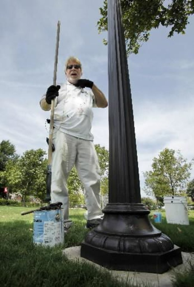 Randy France, University of Oklahoma Facilities Management worker, takes a break from painting outdoor light fixtures as he attempts to survive the hot weather on Tuesday, July 31, 2012, in Norman, Okla. Photo by Steve Sisney