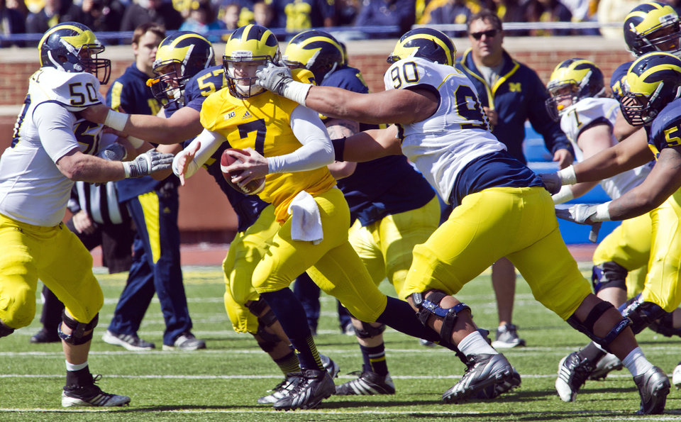 Photo - Michigan quarterback Shane Morris (7) has his face mask pulled by defensive tackle Bryan Mone (90) during the football team's annual spring game on Saturday, April 5, 2014, in Ann Arbor, Mich. (AP Photo/Tony Ding)