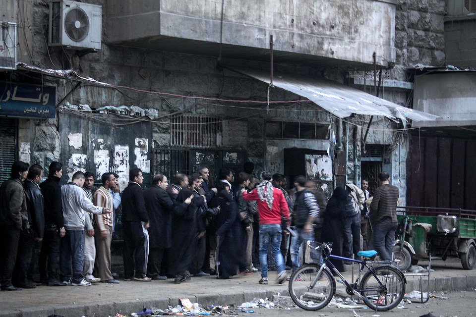 In this Monday, Dec. 3, 2012 photo, Syrian residents stand in line outside a bakery during heavy fighting between Free Syrian Army fighters and government forces, unseen, in Aleppo, Syria. (AP Photo/Narciso Contreras)