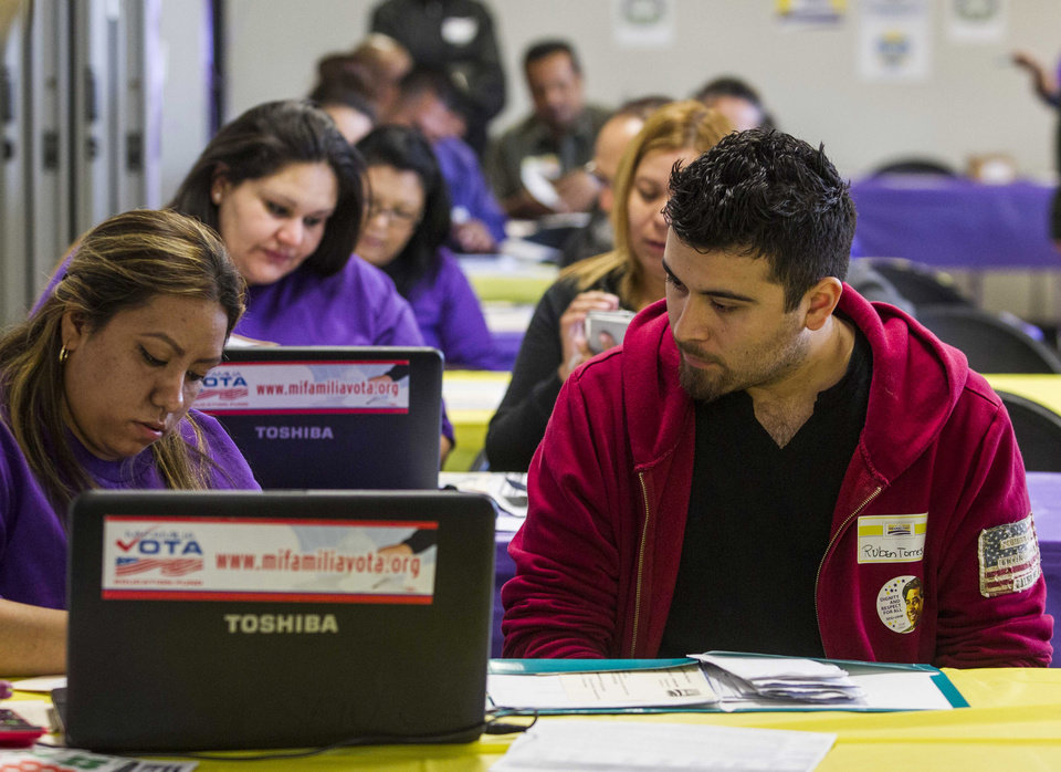 Photo - SEIU-UHW worker Kathy Santana, left , assists Ruben Torres, 27, during a health care enrollment event at SEIU-UHW office, Monday, March 31, 2014, in Commerce, Calif.  Monday is the deadline to sign up for private health insurance in the new online markets created by President Barack Obama's health care law. (AP Photo/Ringo H.W. Chiu)