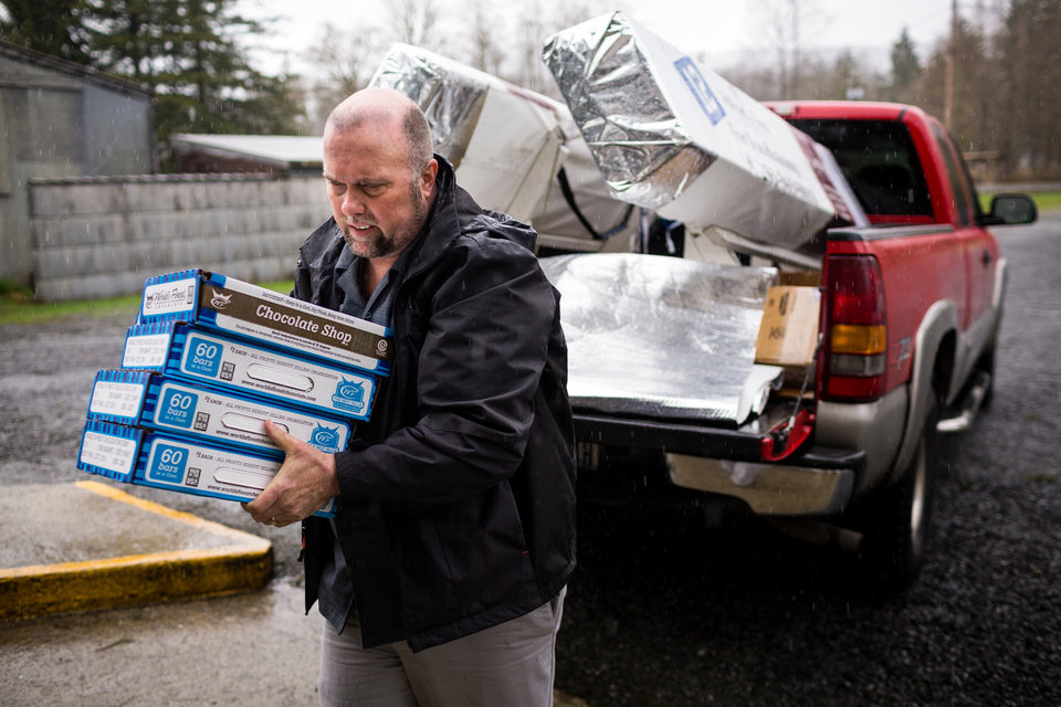 Photo - Gary Ray, pastor of the Oso Community Chapel, helps to load in a truck-full of chocolate bars as a donation for victims to serve as