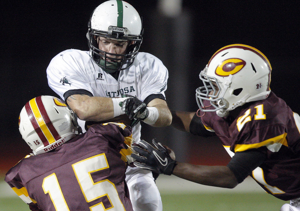 Photo - Catoosa Cole Scheulen is tackled by Clinton's Jake Reynolds (15) and Jalee Rainge tackle during the high school playoff game between Clinton and Catoosa at Putnam City High School.,  Friday, Nov. 25, 2011.  Photo by Sarah Phipps, The Oklahoman
