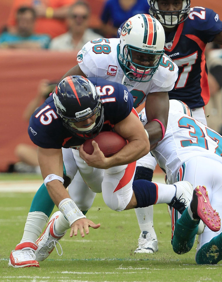 Photo -   Denver Broncos quarterback Tim Tebow (15) is tackled by Miami Dolphins linebacker Karlos Dansby (58) and safety Yeremiah Bell (37) during the first half of an NFL football game Sunday, Oct. 23, 2011, in Miami. (AP Photo/Wilfredo Lee)
