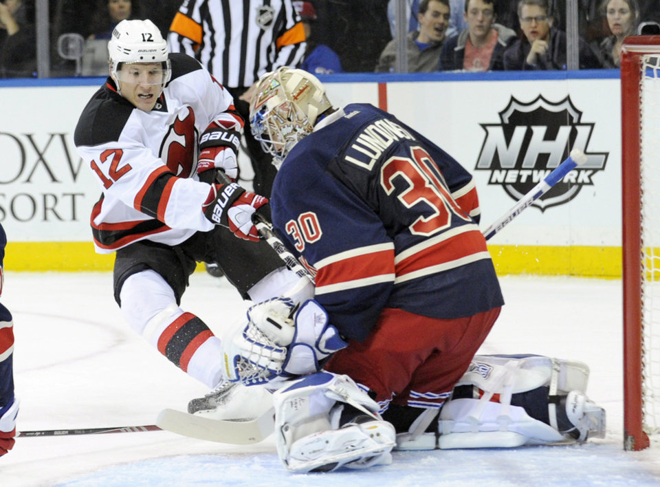 New York Rangers goaltender Henrik Lundqvist, right, of Sweden, makes a save on a shot by New Jersey Devils' Damien Brunner, of Switzerland, during the first period of an NHL hockey game on Saturday, Dec. 7, 2013, at Madison Square Garden in New York. (AP Photo/Bill Kostroun)