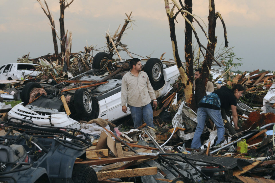 Photo - Residents begin digging through the rubble of their home after it was destroyed by a tornado that hit Joplin, Mo. on Sunday evening, May 22, 2011. The tornado tore a path a mile wide and four miles long destroying homes and businesses. (AP Photo/Mike Gullett) ORG XMIT: MOMG109