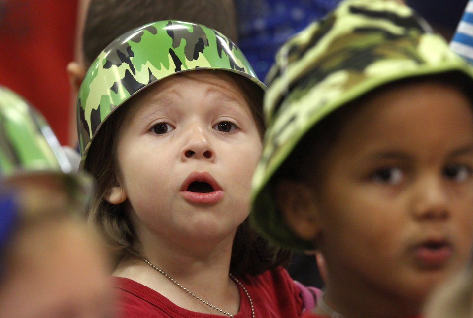 Julia Guitron sings a song while sitting with other kindergarten students during a patriotic-themed Veteran's Day assembly Friday morning, Nov. 9, 2012, at Schwartz Elementary School at SE 104 and Anderson Road.   Many students wore red, white and blue or camouflage to honor veterans.      Photo by Jim Beckel, The Oklahoman