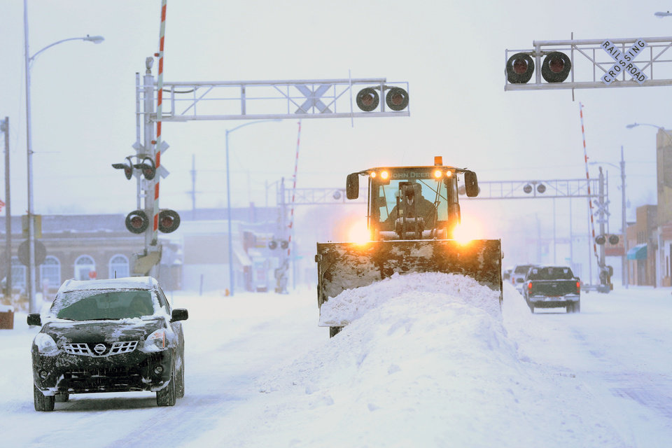 Photo - A City of Hutchison, Kan., front end loader clears snow from intersections on S. Main St. Tuesday, Feb. 4, 2014. The winter storm dumped more than 10 inches of snow on the city from late Monday to late Tuesday. (AP Photo/The Hutchinson News, Travis Morisse)