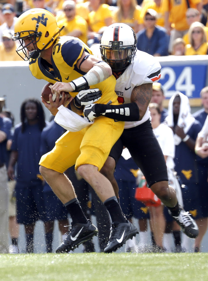 Oklahoma State's Shamiel Gary (7) pulls down West Virginia's Clint Trickett (9) during the second half of a college football game between the Oklahoma State University and West Virginia University on Mountaineer Field at Milan Puskar Stadium in Morgantown, W. Va.,   Saturday, Sept. 28, 2013. Photo by Sarah Phipps, The Oklahoman