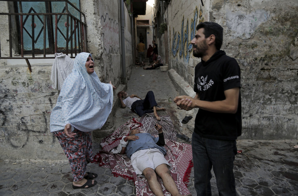 Photo - A Palestinian woman reacts while standing next to two injured men as they lay on the ground and wait for help following an Israeli strike in the Shijaiyah neighborhood, eastern Gaza City, Wednesday, July 30, 2014. Israeli strikes hit a crowded shopping area in the neighborhood, hours after tank shells tore through the walls of a U.N. school crowded with war refugees Wednesday in the deadliest of a series of air and artillery attacks that push the Palestinian death toll above 1,300 in more than three weeks of fighting. (AP Photo/Adel Hana)