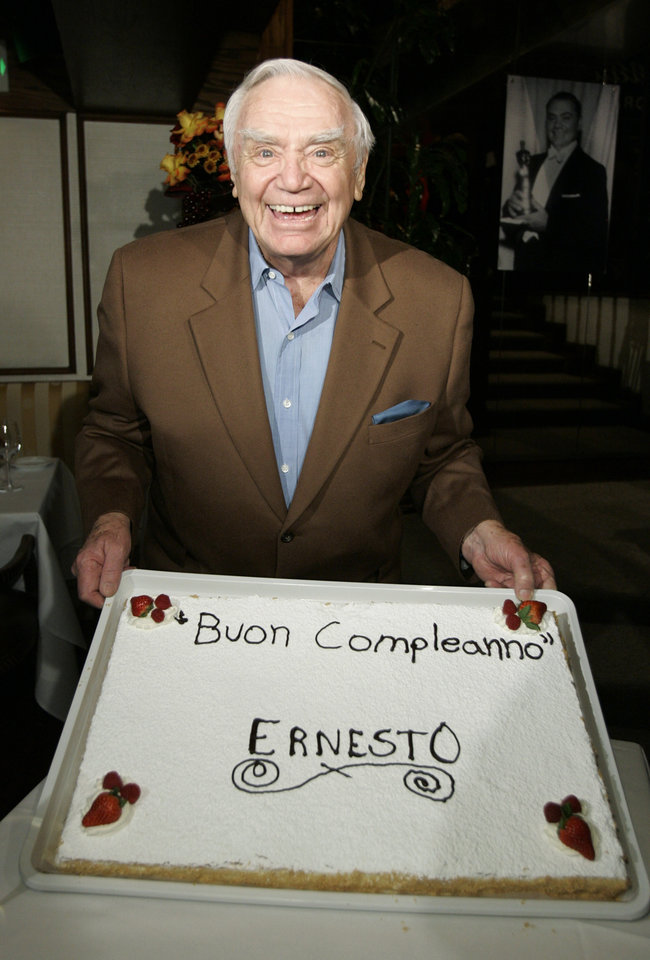 Photo - Ernest Borgnine holds up his cake as he celebrates his 90th birthday during a party at Madeo's restaurant in Los Angeles, Wednesday, Jan. 24, 2007. (AP Photo/Kevork Djansezian) ORG XMIT: KSD101