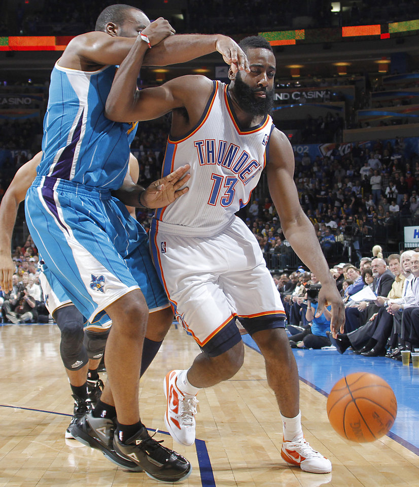 Oklahoma City Thunder guard James Harden (13) is fouled by New Orleans Hornets power forward Carl Landry (24)during the NBA basketball game between the Oklahoma City Thunder and the New Orleans Hornets at the Chesapeake Energy Arena on Wednesday, Jan. 25, 2012, in Oklahoma City, Okla. Photo by Chris Landsberger, The Oklahoman