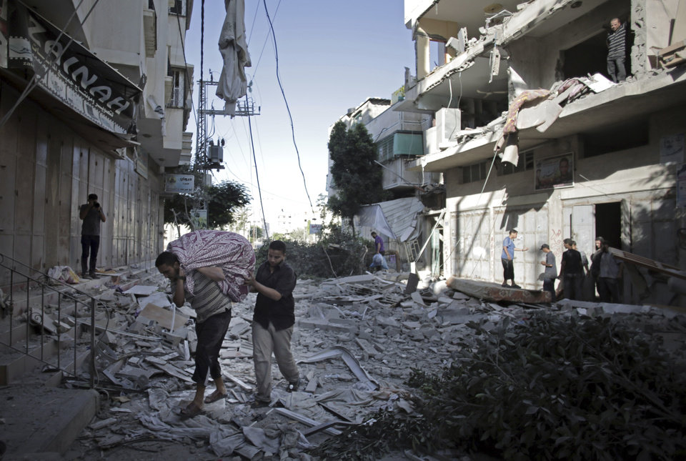 Photo - Palestinians salvage what they can of their belongings from the rubble of their destroyed house following an early morning Israeli missile strike in Gaza City, Wednesday, July 16, 2014. A Hamas website says Israel has fired missiles at the homes of four of its senior leaders as it resumed bombardment of Gaza, following a failed Egyptian cease-fire effort. Health officials say the Palestinian death toll in nine days of fighting has reached 204.(AP Photo/Khalil Hamra)