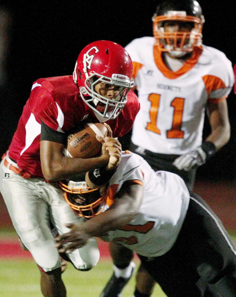 Photo - Carl Albert's Dillan Dansby is brought down by William Whayne of Booker T. Washington during a high school football game in Midwest City, Okla., Friday, September 3, 2010.  Photo by Bryan Terry, The Oklahoman