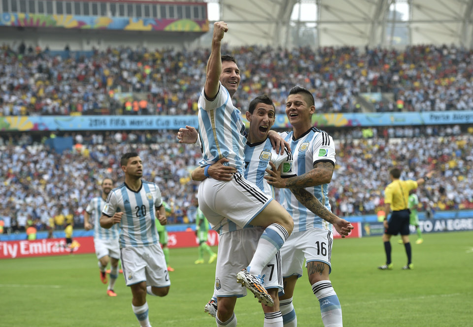 Photo - Argentina's Lionel Messi, left, is carried by his teammates Argentina's Angel di Maria (7) and Argentina's Marcos Rojo after scoring his side's first goal during the group F World Cup soccer match between Nigeria and Argentina at the Estadio Beira-Rio in Porto Alegre, Brazil, Wednesday, June 25, 2014. (AP Photo/Martin Meissner)